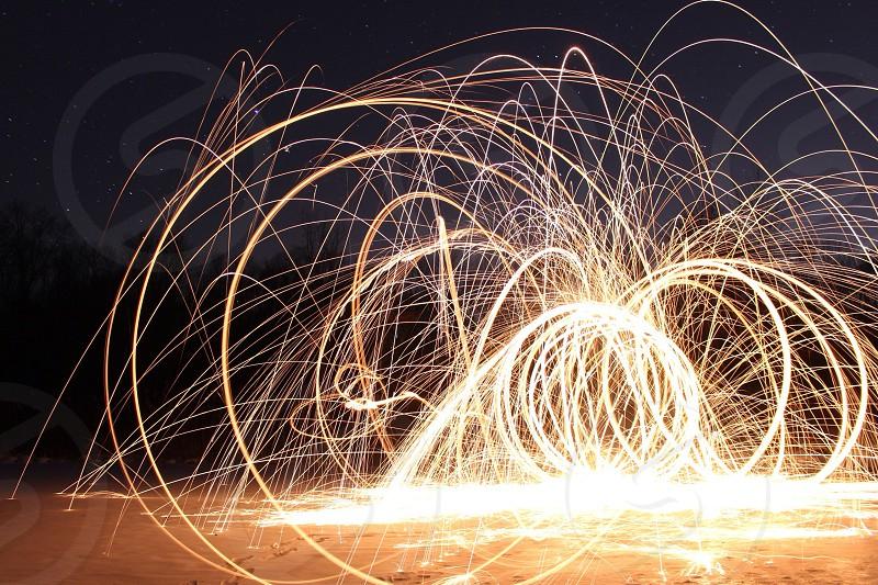 gold sparklers making arcs through black sky photo