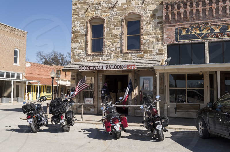 Group of motorcycles parked outside of the Stonewall Saloon in the small old west town of Saint Jo Texas on a sunny day. photo