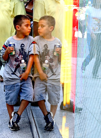 A little boy on a busy street is reflected in a big picture window he is leaning against. photo
