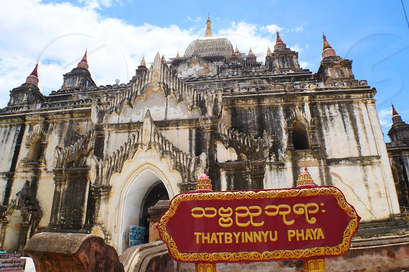 """Thatbyinnyu Temple Sabbannu or """"the Omniscient"""" is a famous temple located in Bagan (formerly Pagan) built in the mid-12th century during the reign of King Alaungsithu.[1]:166–167 It is adjacent to Ananda Temple. Thatbyinnyu Temple is shaped like a cross but is not symmetrical. The temple has two primary storeys with the seated Buddha image located on the second story. photo"""