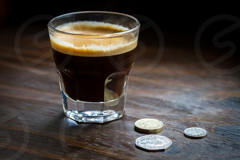Coffee : a short coffee an espresso served in a glass with a few English pound coins on a wooden table.  PS : no need for a model release - no one. photo