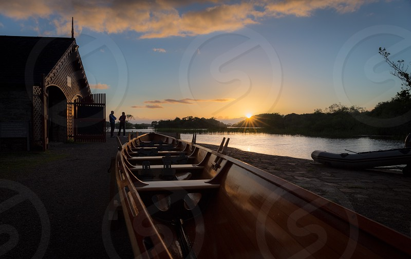 White Clouds and Sun Over Water and Canoes photo