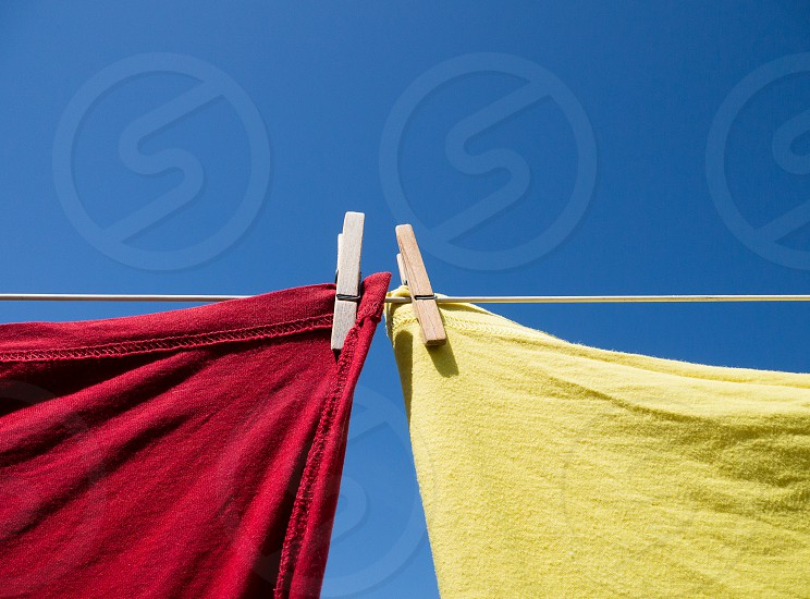 One red and one yellow T-shirt hanging on a clothesline with wooden clothes pegs shot in colour from below with a clear blue sky behind photo