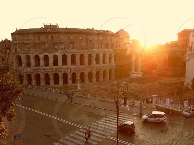 Sun setting behind Colosseum / Roman Forum in Rome photo