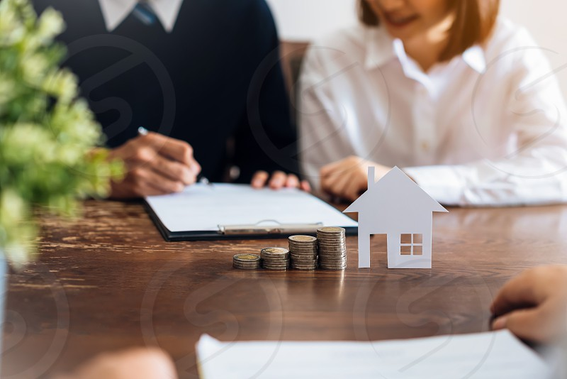 Couples signed a contract to buy a house from the broker. Coin to stack money and model houses placed on the table financial Business Growth. photo