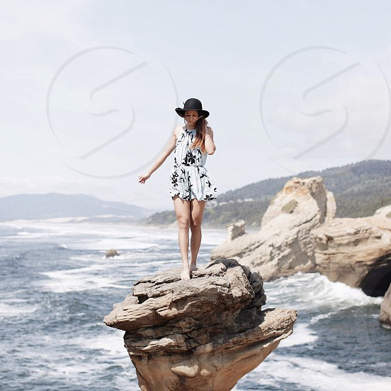 woman wearing white and black floral halter neck romper in the standing in the middle of rock formation behind body of water photo