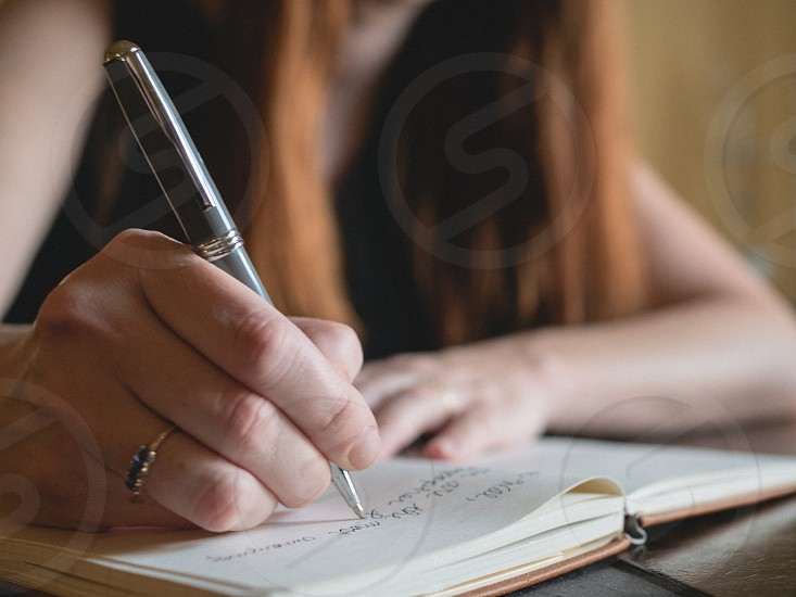 A woman writing in a journal.  photo