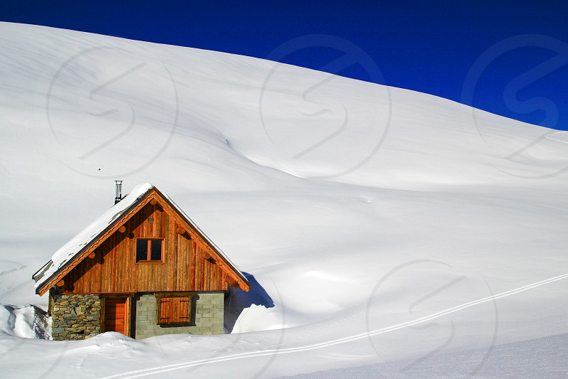 isolated cabin high up in the mountains surrounded by untouched snow photo