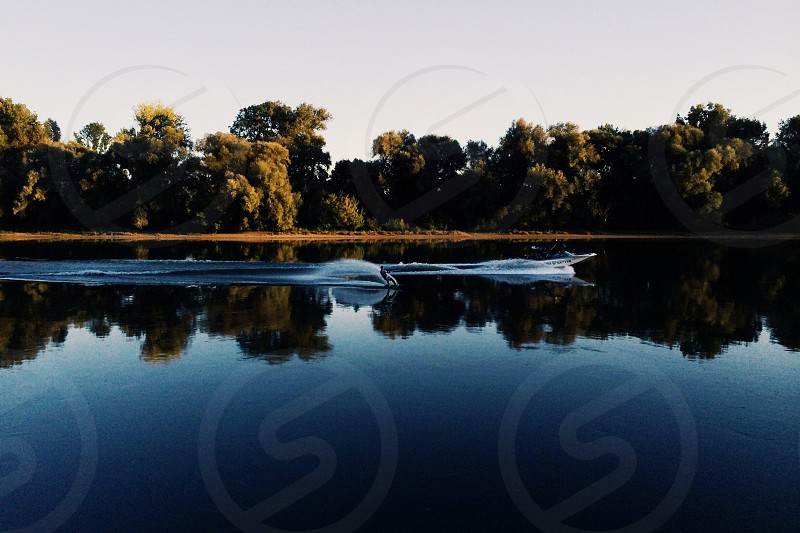waterskier and boat on danube river symmetric reflection photo