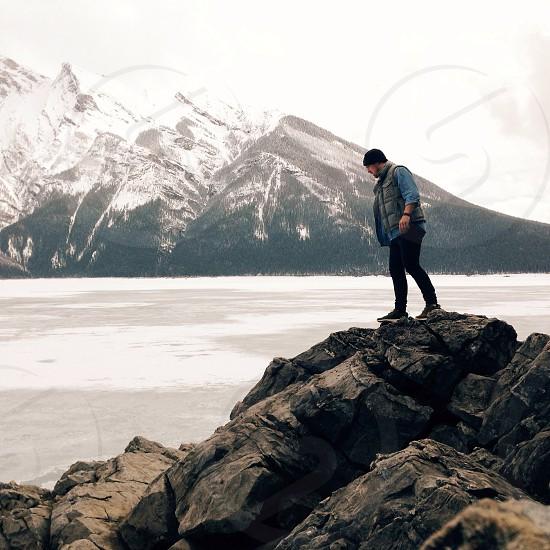 man standing on black rocks photo