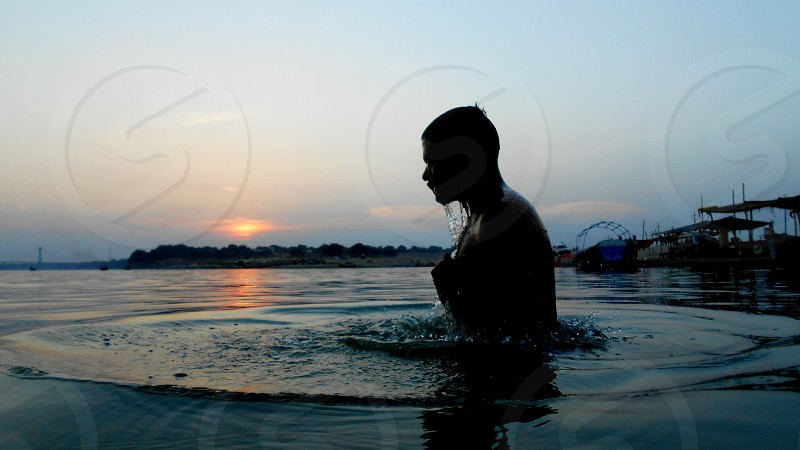 A saint taking a dip in the holy Ganges      photo
