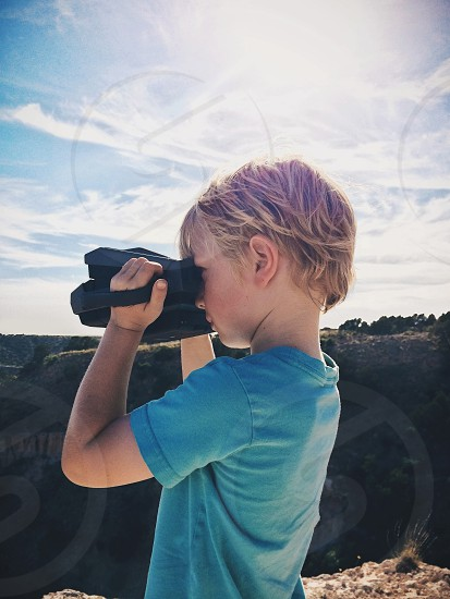 A young boy takes a landscape photo with an instant camera.  photo