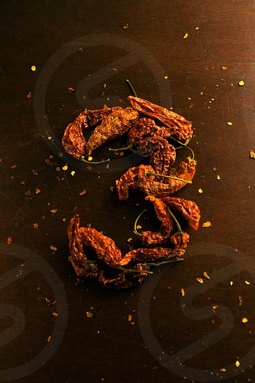 The number 3 formed from a group of ghost chilies on a dark wooden background; surrounded by pepper flakes photo