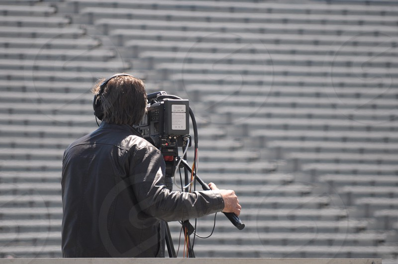 camera man wearing black leather jacket is taking a video of a stadium seat during daytime photo