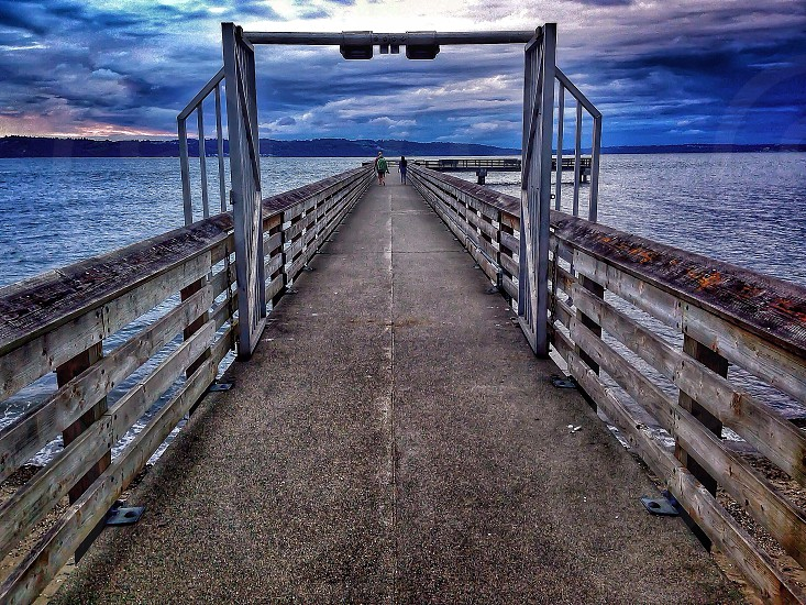 first person perspective photography of bridge on body of water photo