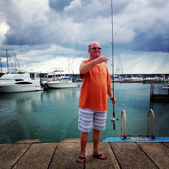 Michigan water sun fish hobby man fishing happy relaxingboats dock photo