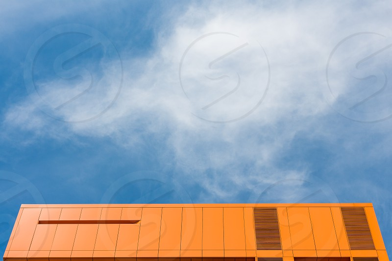 Top of orange building and blue sky photo