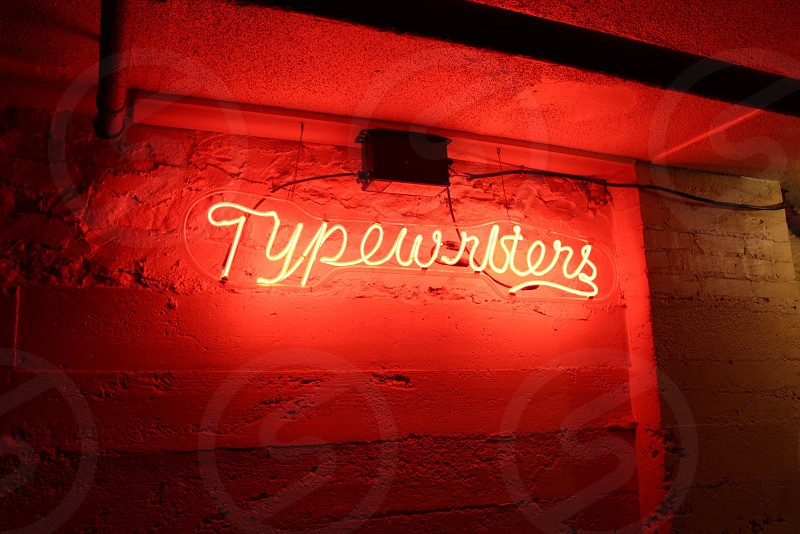 Red neon sign that says Typewriters photo