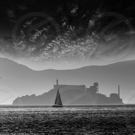 Alcatraz island penitentiary at sunset backlight sailboat in san Francisco California USA photo