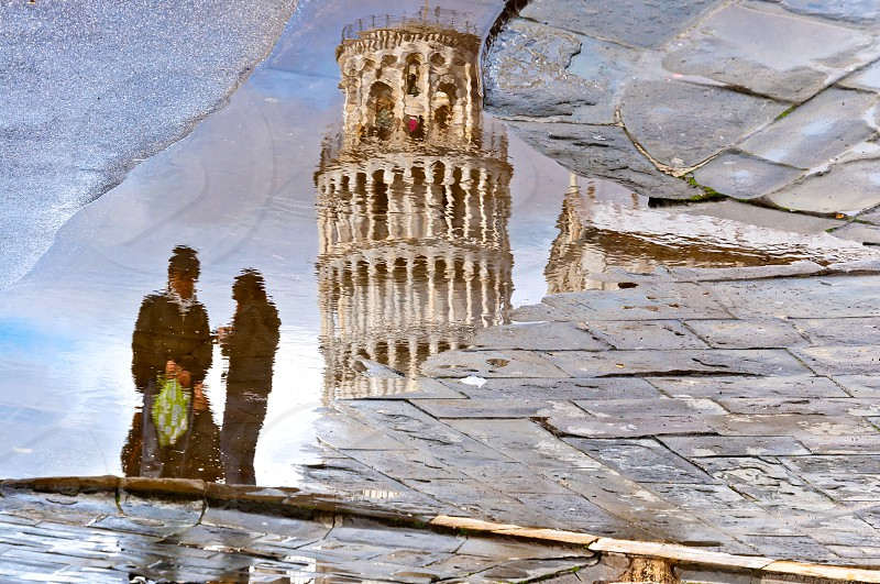 reflection of famous leaning tower and couple of unidentified tourists in a puddle on March 18 2013 in Pisa. photo