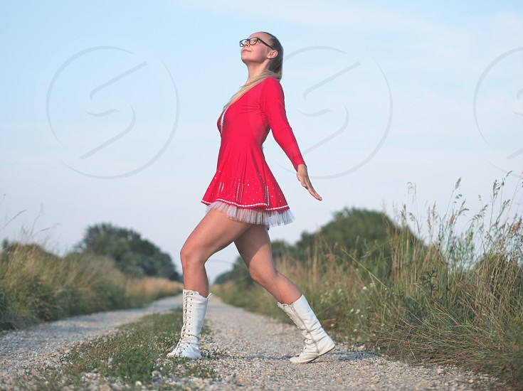 Bespectacled Blonde Teen Majorette Girl Outdoors in Red Dress photo