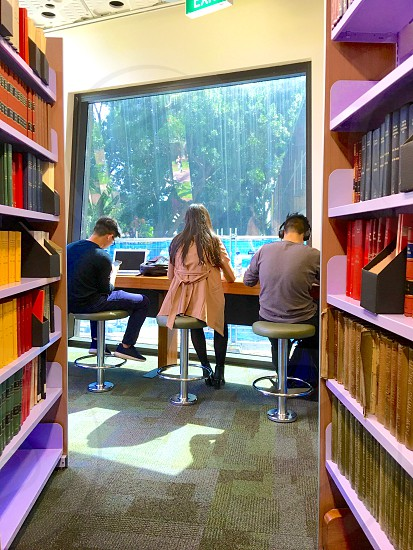 Studying study education college university students student life library books window natural light headphones sitting table using technology headphones laptop real life candid photo