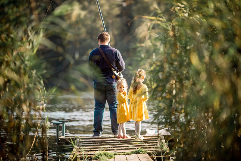 Family fishing on a lake at autumn day photo