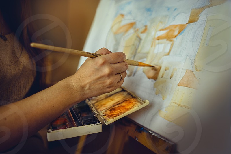 Artist painter easel watercolor people woman created creativity picture paper dark wood wooden aquarelle detail brush  hand  photo