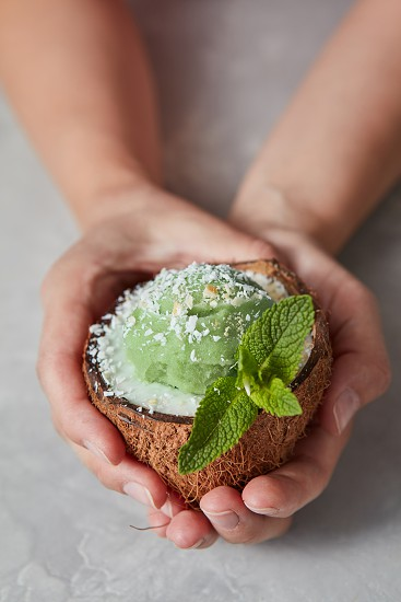 Mint green ice cream homemade in a coconut shell in the woman hands on a gray concrete background. Summer dessert for vegetarian. photo