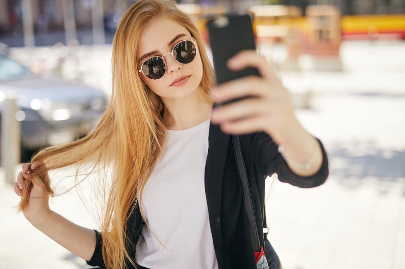 Pretty blonde girl taking selfie on the street photo