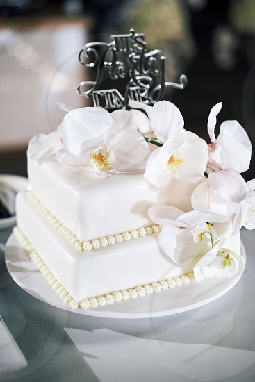 """The white wedding cake 2 layers and the white orchids decoration with text """"it's party time"""" on top photo"""