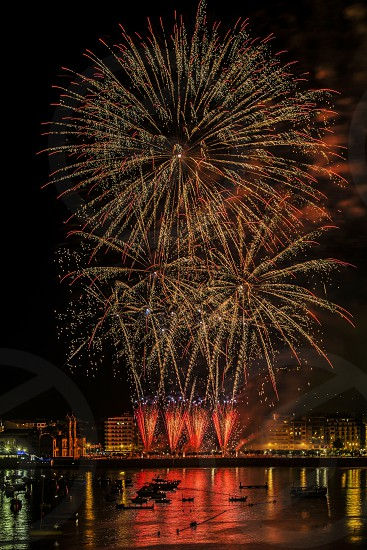 beige and orange fireworks display on sky above body of water and structures photo