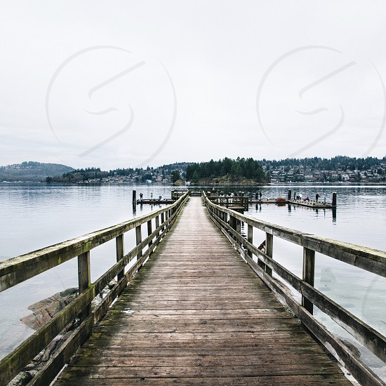 wood pier into a lake with homes and trees on a hill in the distance under a white sky photo