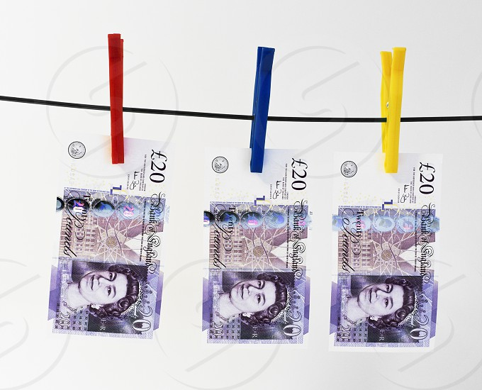 Twenty pound notes hanging on a washing line by different coloured pegs photo