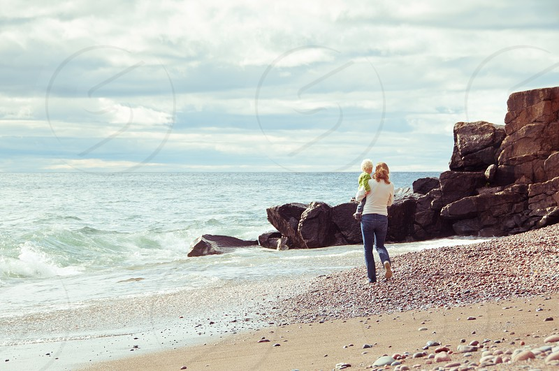 authentic travel beach shore sand rocks water lake ocean waves summer vacation fall autumn landscape woman child boy mother son walking carry holding female jeans photo