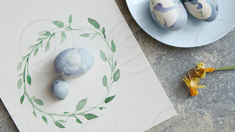 homemade easter eggs on a paper and plate on the stone background flat lay photo