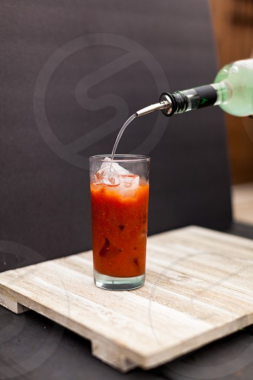pouring vodka into a glass bloody mary photo