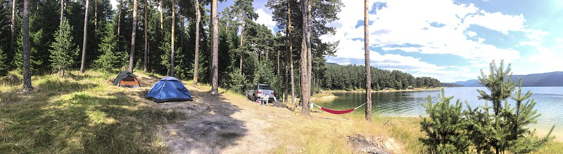 Panoramic image of forest and mountain lake. Tents and car in the wild nature. Sunny day. Many pine trees. Panorama in the forest. photo