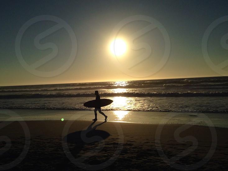 A surfer walks on the beach near sunset. California. photo