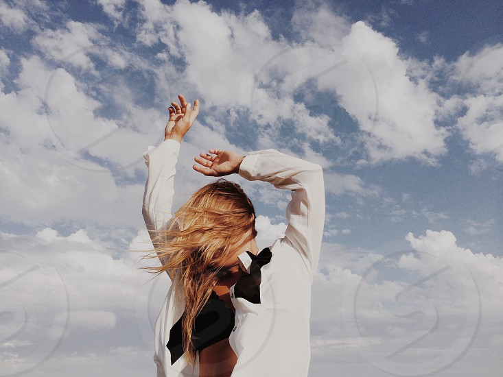 woman in white coat with arms up under blue cloudy sky photo