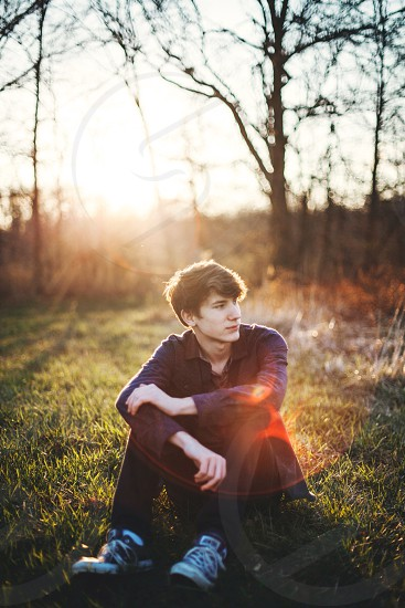 man sitting on green grass photo