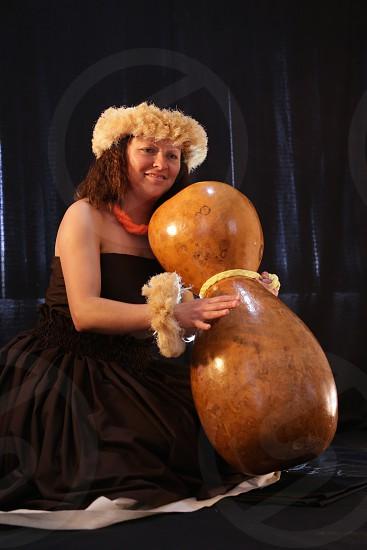Smiling female Hawaiian girl dancing and singing with musical instruments like the ukulele photo