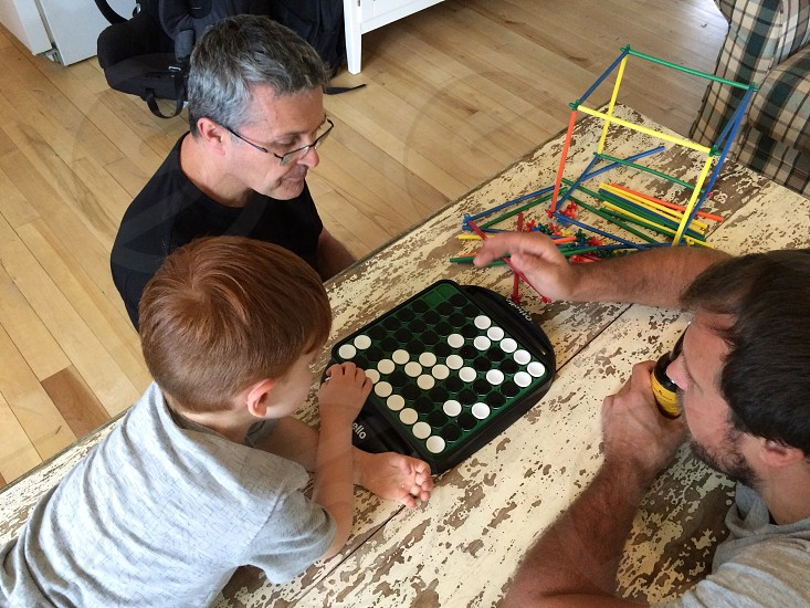 Grandfather son and grandson playing a game at the cottage. photo