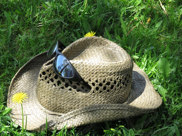 A tan colored straw cowboy hat with sunglasses in the grass on a sunny summer day. The view in the glasses is a tree with a clothesline of bedsheets blowing in the wind. Nature dandelions wild west photo