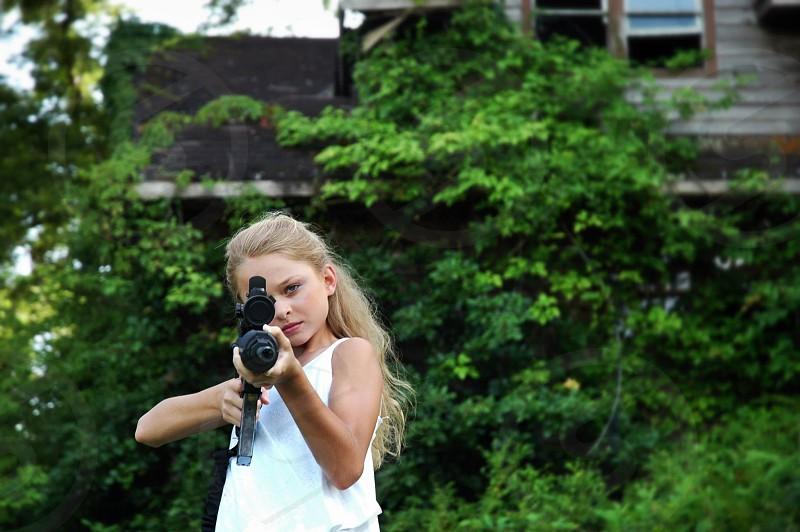 Girl gun shoot aim fire weapon danger innocent controversy gun control ar-15 rural overgrown abandoned  photo