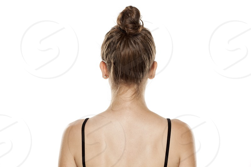 Rear view of young woman with bun on white background photo