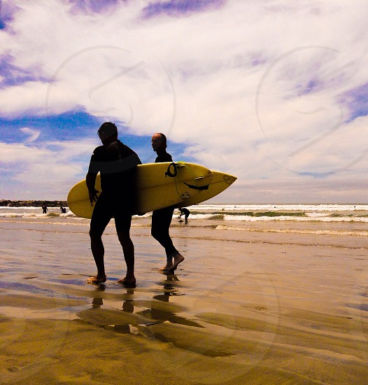 surfers walking along the beach photo