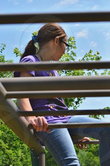 girl sitting on monkey bar photo
