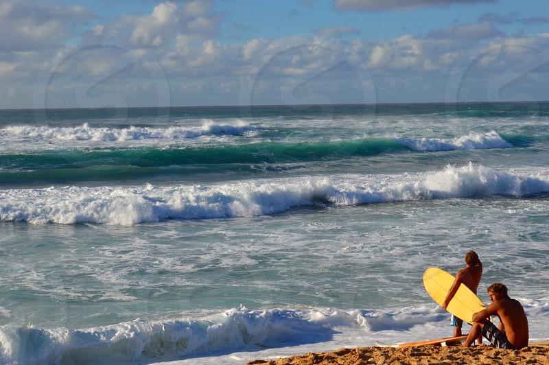 2 men on seashore with surf board photo