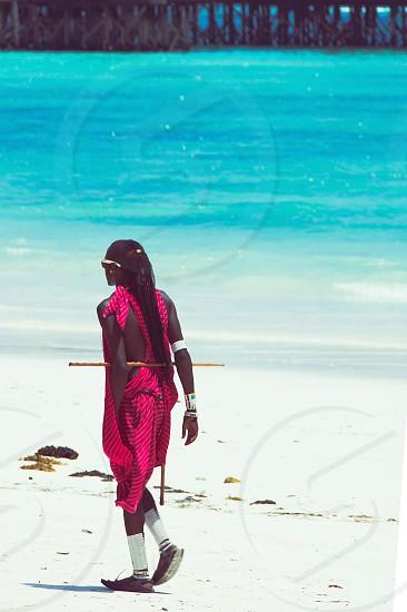 Lonely Masai walking on white tropical beach of Zanzibar island - Tanzania photo